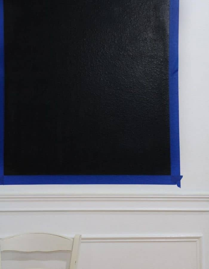 This is an up close image of the painters tape on the wall and the freshly painted chalkboard.
