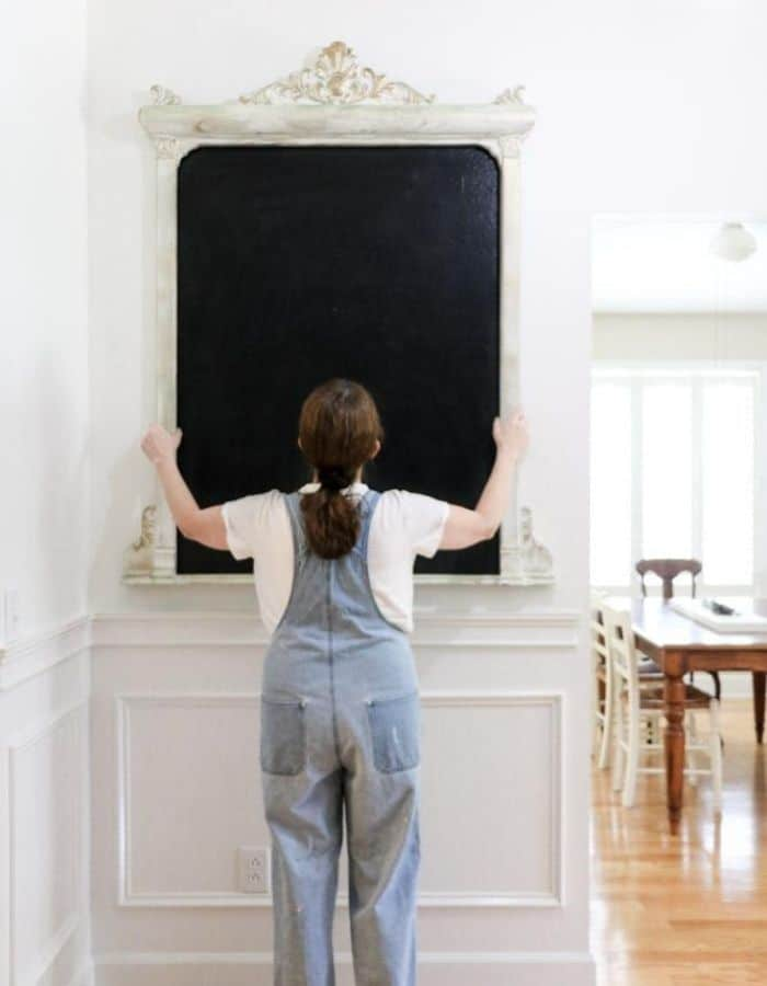 Hanging a frame over a painted home made chalkboard on the wall.