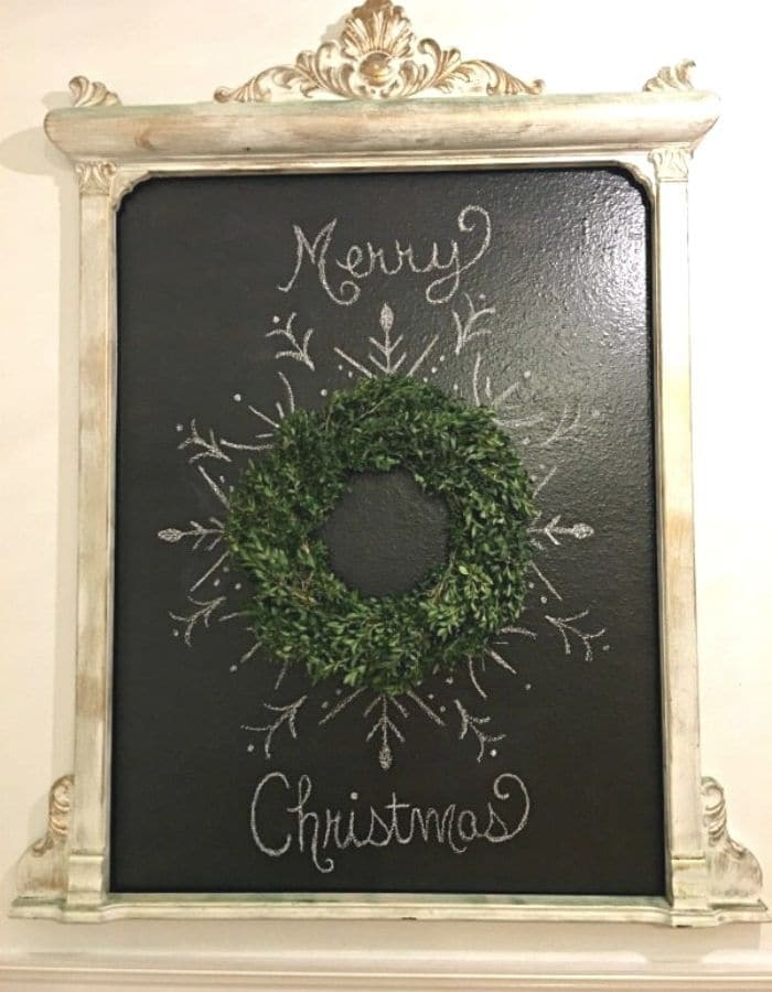 Homemade chalkboard that says 'Merry Christmas' on it written in cursive. In the center is a boxwood wreath with a pretty design boarding the wreath to resamble a snow flake.