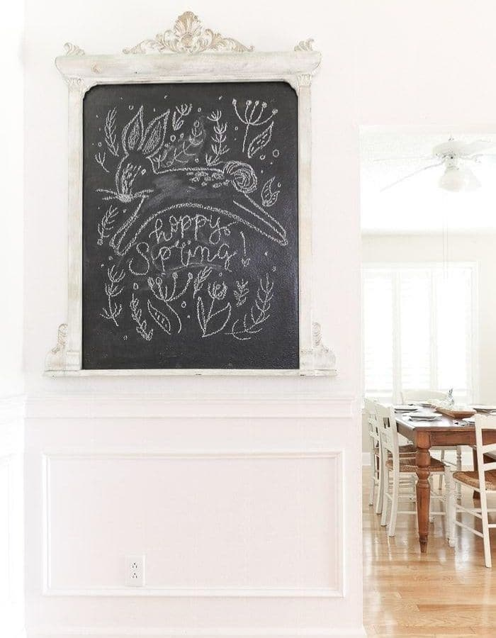 DIY chalkboard that says 'hoppy Spring' written in cursive below a leaping bunny. Around the text and bunny, greenery is drawn in the chalk.