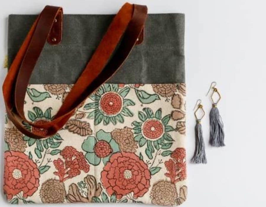Fair Trade Friday subscription box, Small floral and grey purse with leather straps along with a pair of tassel earrings.