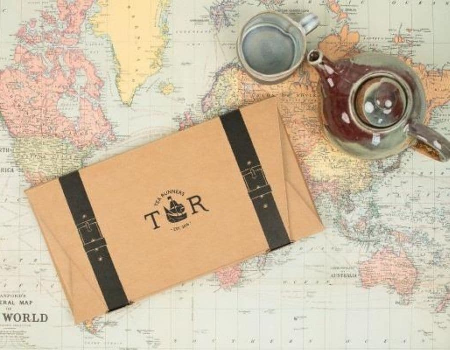 Tea Runners monthly loose leaf tea gift subscription on top a world map with a tea pot next to it.