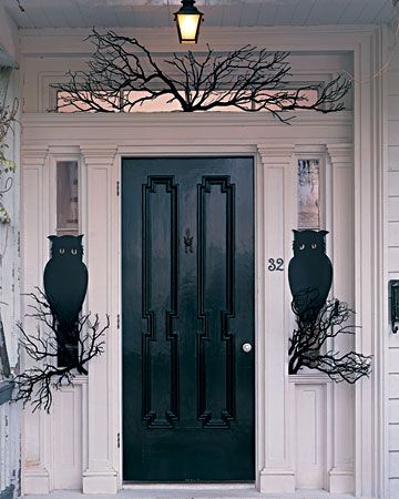 Front porch Halloween decoration ideas.  Black front door on a porch with branches painted black and silhouettes of owls sitting on the branches looking at guest who arrive.