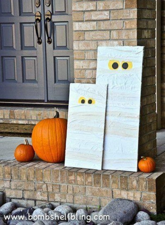 Cute DIY Halloween mummies made wtih wood and paper sitting on a front porch with pumpkins.
