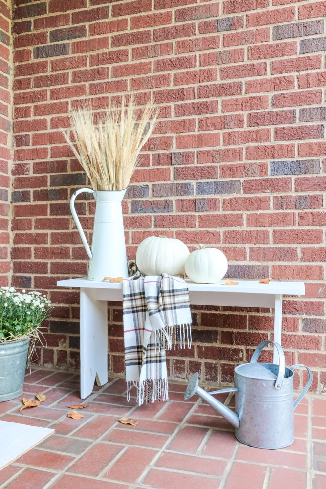 Fall front porch accessories of pumpkins, scarf, and french pitcher filled with wheat