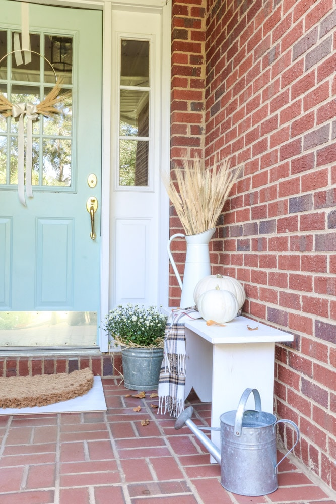 An autumn front door and porch with a little white bench, mums, pumpkins, and dried wheat.