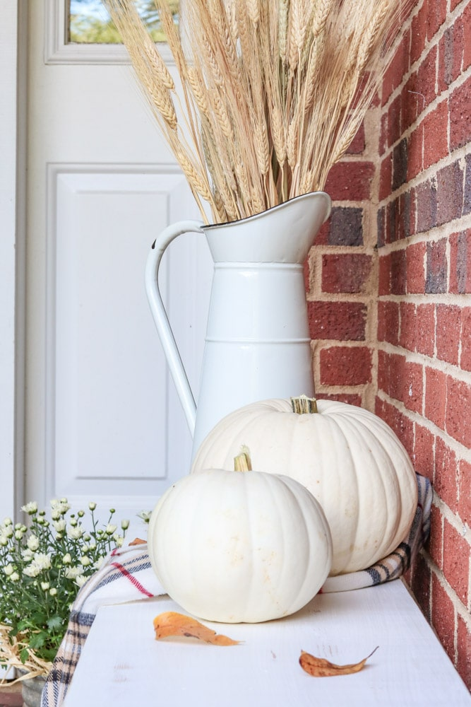 White pumpkins sitting on a farmhouse bench on a tiny front porch for autumn