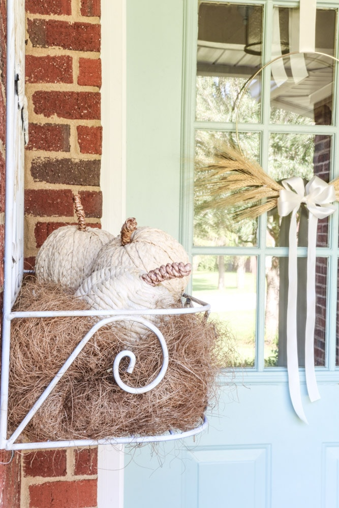 Faux pumpkins wrapped in a natural twine sitting inside a iron wall flower hanger on a front porch for fall.