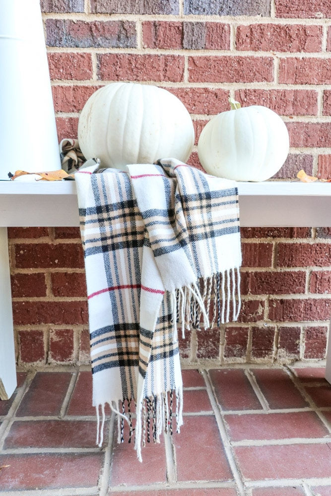 Fall decorations of a white pumpkins and a scarf on a farmhouse bench