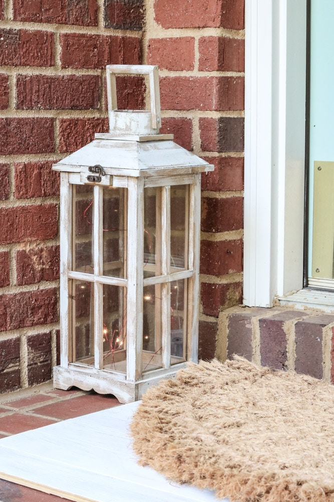 Small front porch decor using a painted lantern with mini lights inside.