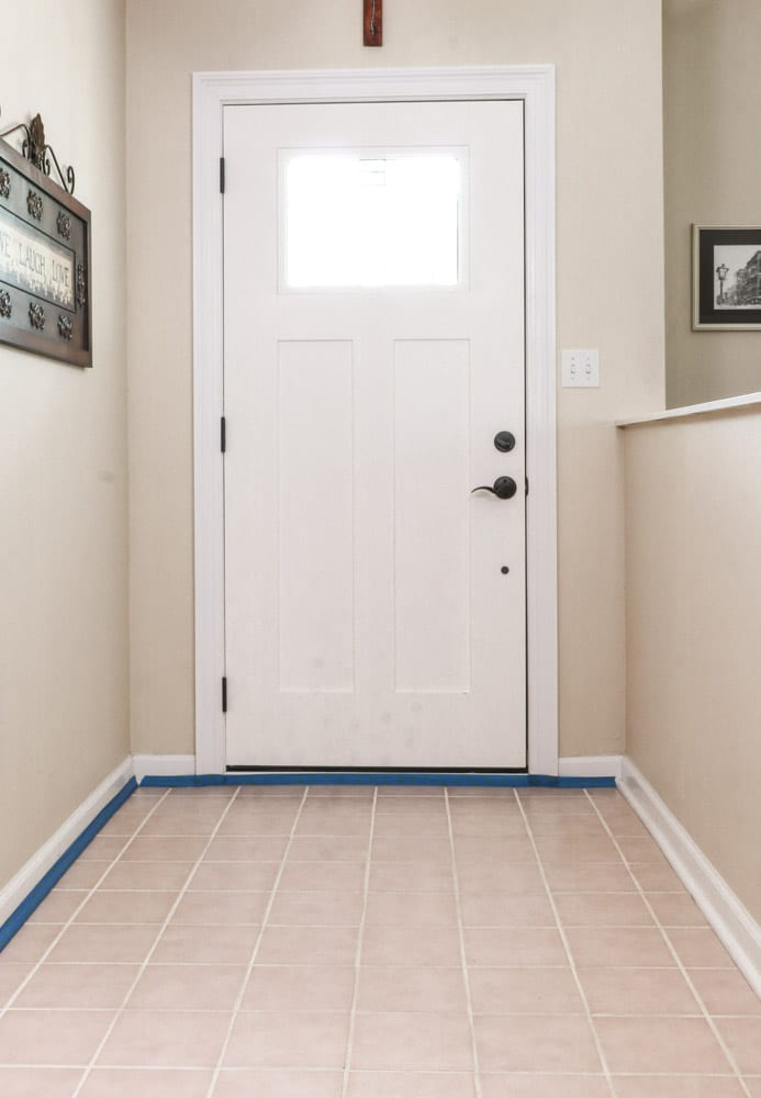 Paint over tile floors by taping the baseboard first