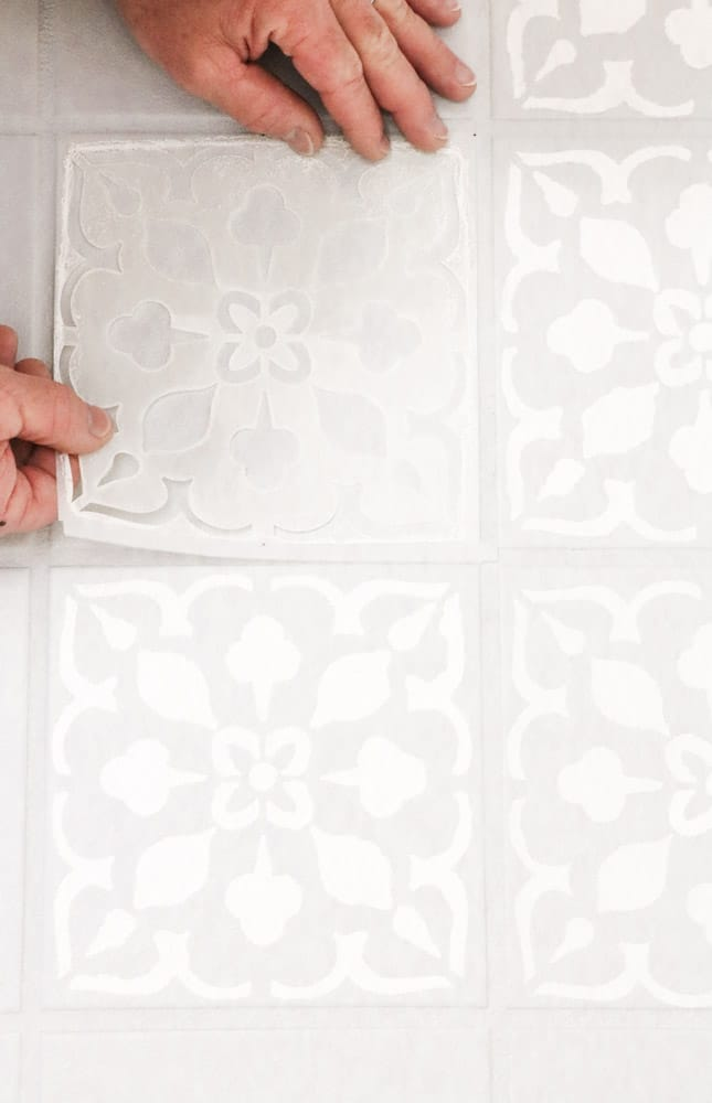 Place stencil in the center of a tile to paint the tile floor with a stencil
