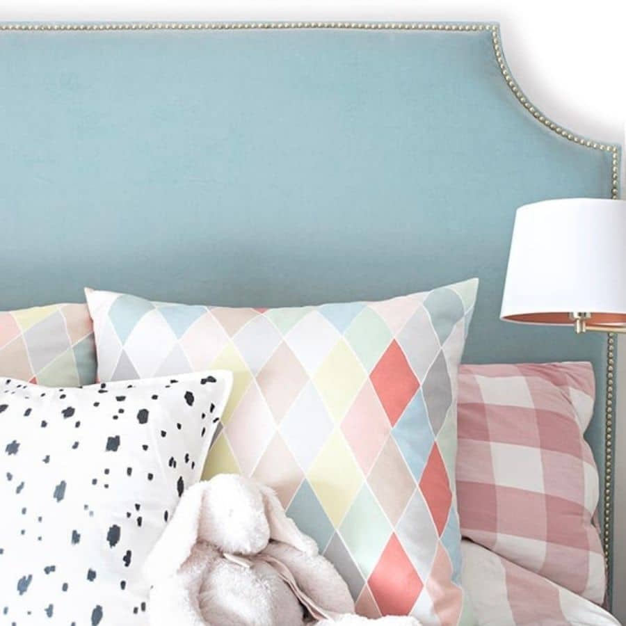 A DIY upholstered headboard with a studded nail trim.