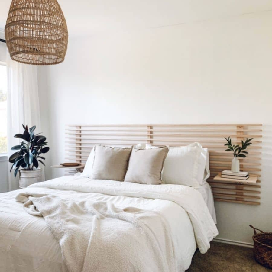 A DIY headboard made out of wooden slates that also creates little floating nightstands.