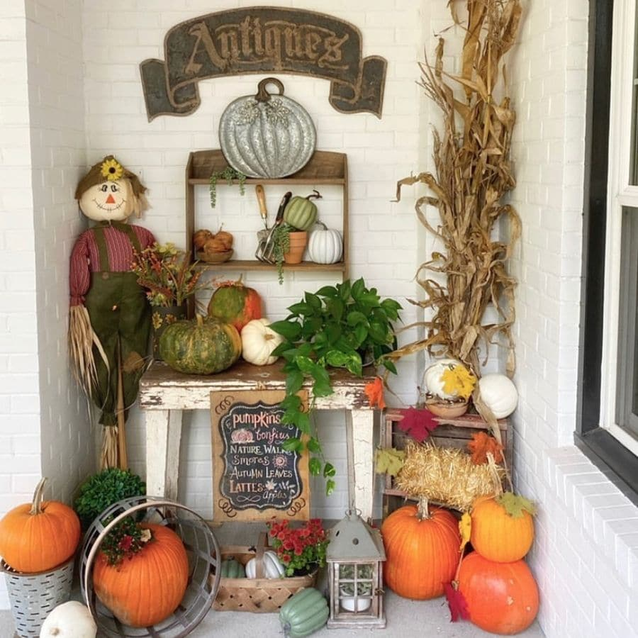 A fall styled nook on a front porch filled with decorations like pumpkins and a scarecrow.