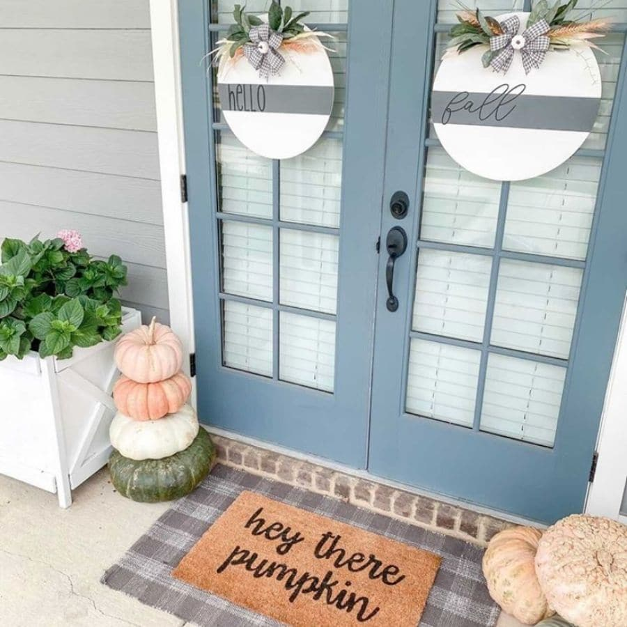 Another fall front door decor with layered mats and stacked pumpkins.