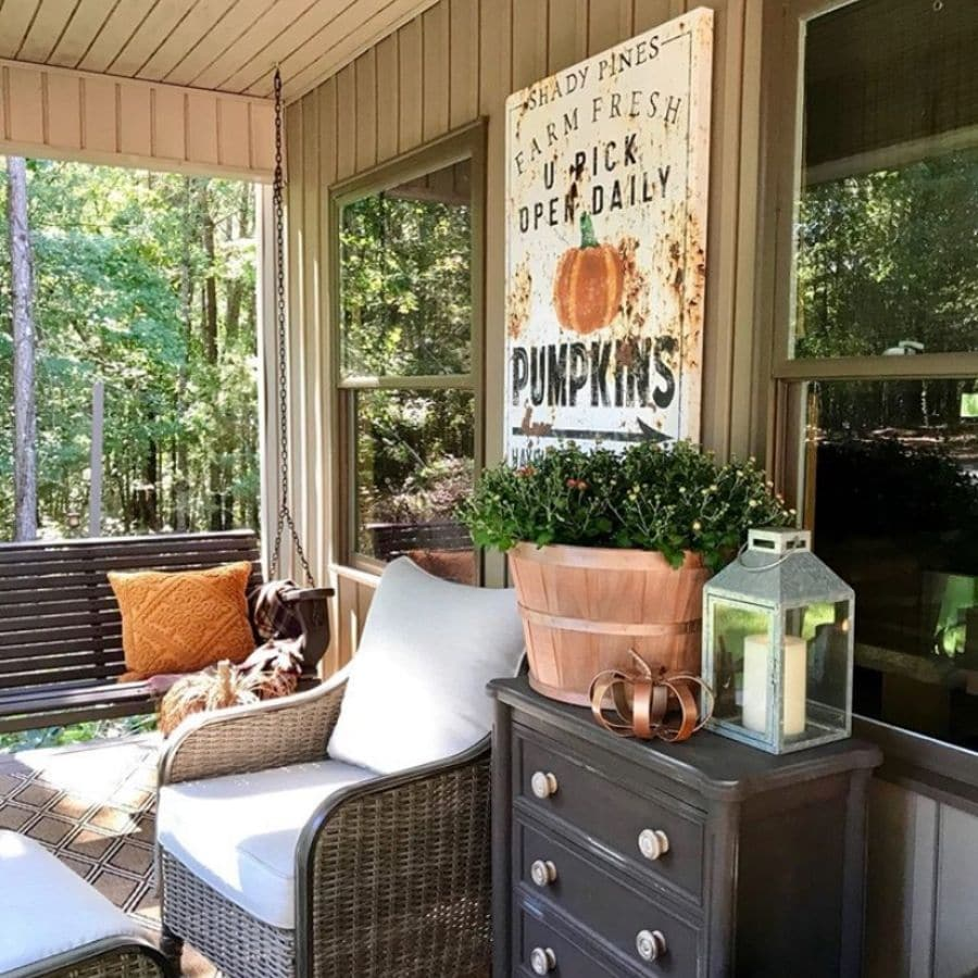 A fall front porch with a vintage pumpkin farm sign hanging on the wall.