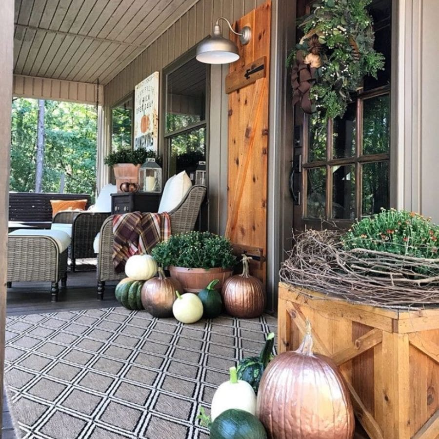 A rustic vintage fall front door and porch with a few planters of mums and metallic painted pumpkins.