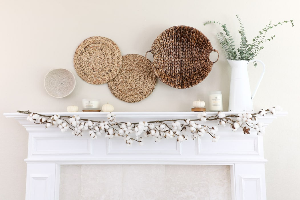 Baskets, candles, and cotton garland on a fall mantle.