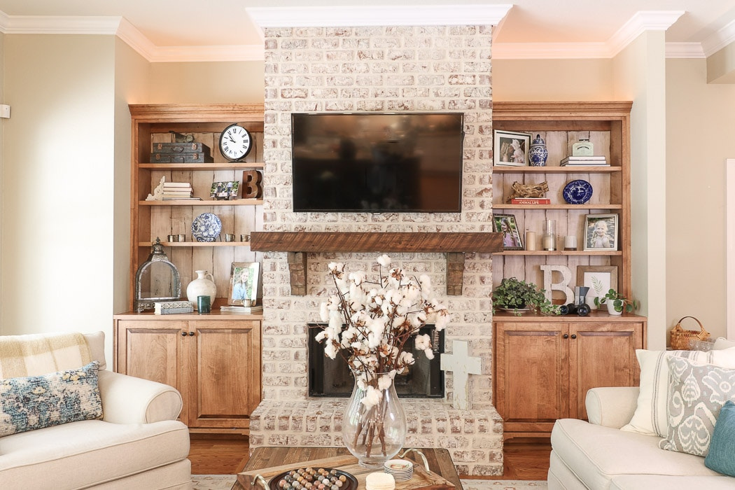 Accessorized bookcases on each side of a fireplace