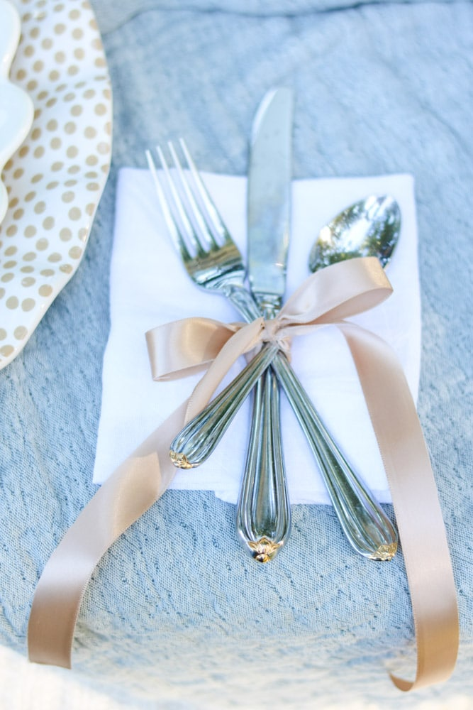Silverware wrapped in ribbon and tied in a tow for a fall or Thanksgiving tablescape