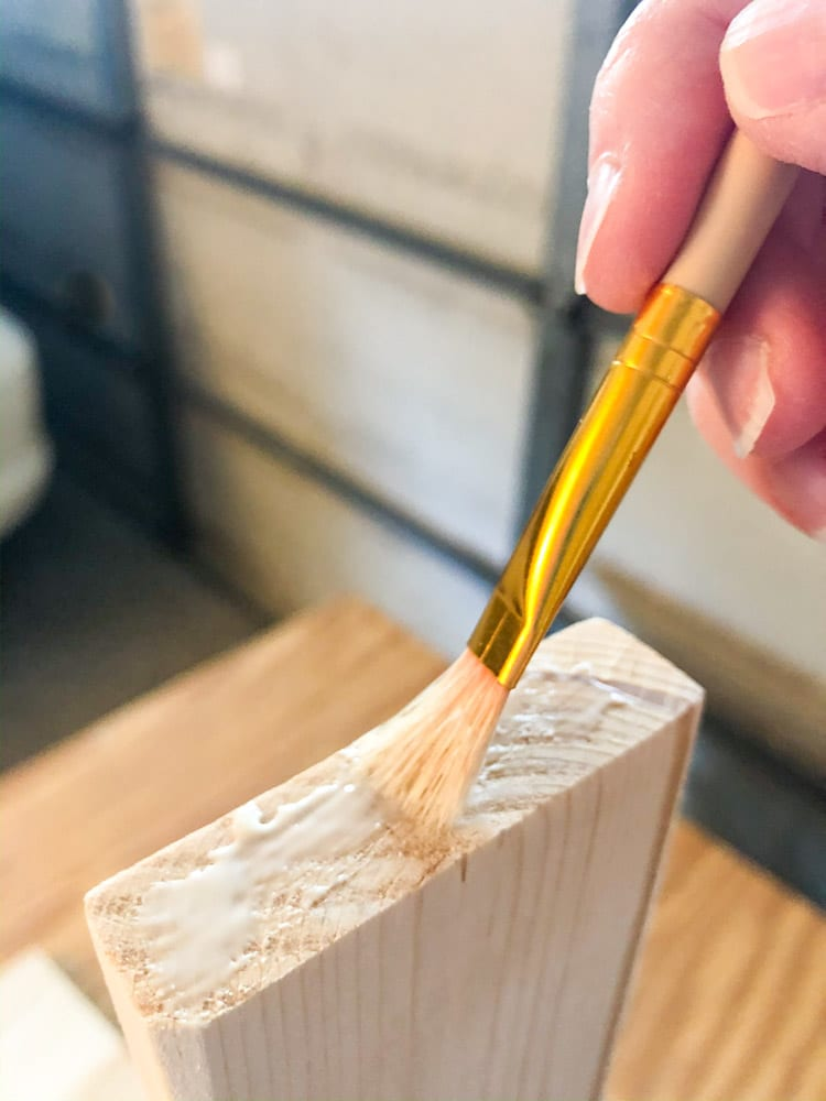 Applying glue to a piece of wood for a wood bench