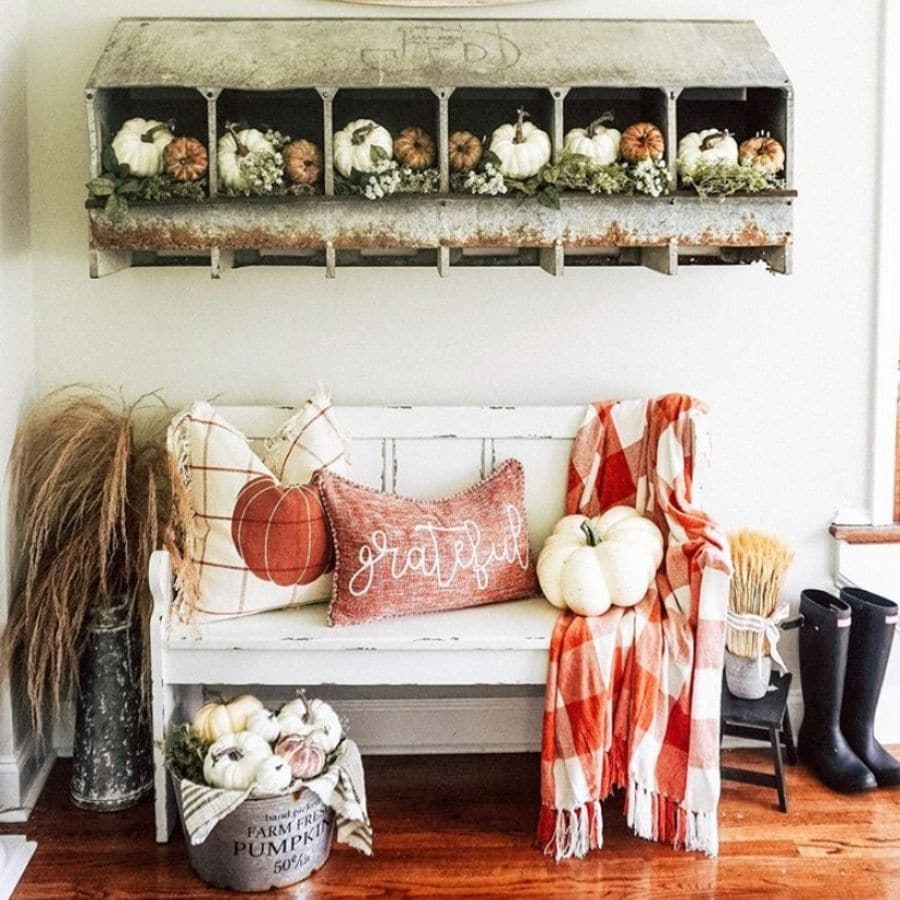 A farmhouse bench decorated for fall.