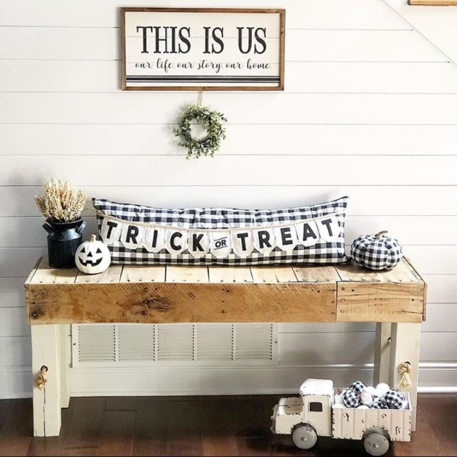A wooden bench decorated with a bolster pillow and halloween decor.