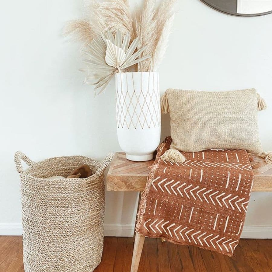 A wooden bench styled with a blanket, pillow, basket, and tall vase.
