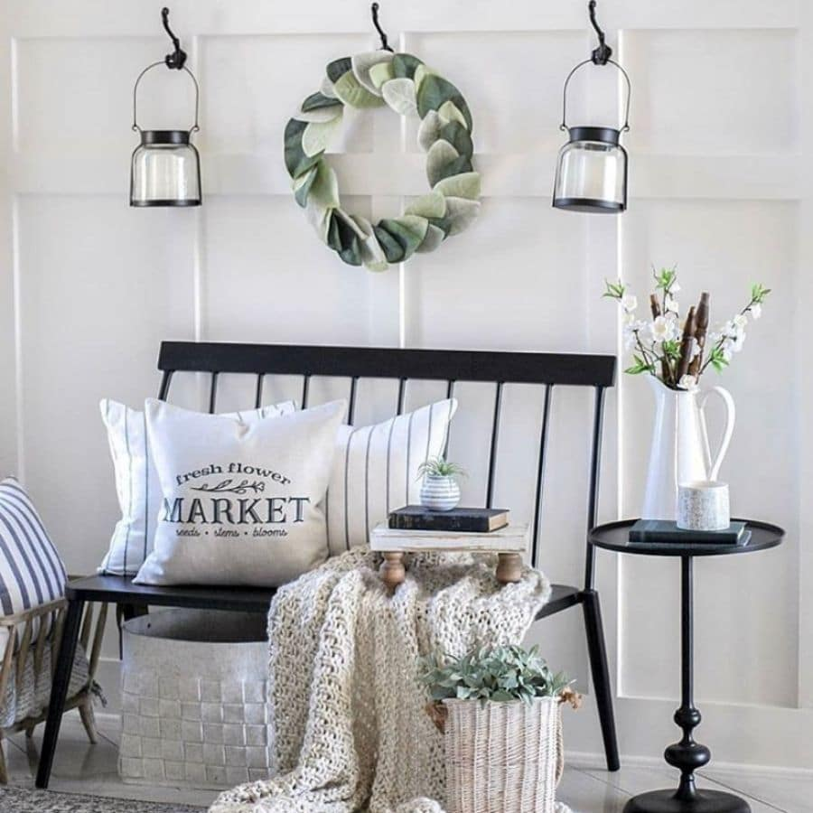 A black bench styled with a chunky throw blanket and books ad pillows.