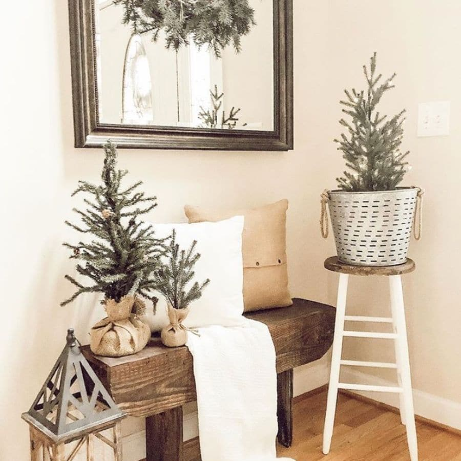 A pretty wooden bench with pillows a blanket and a few mini trees on it, perfect for Christmas.