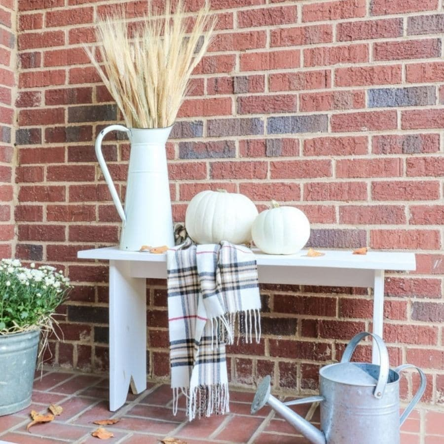 Our DIY wooden bench with fall decor on it like pumpkins and a scarf.