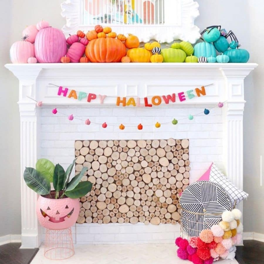 Pumpkins painted in rainbow color sitting on a white fireplace mantle.  Happy Halloween garland hanging on front of the mantle.