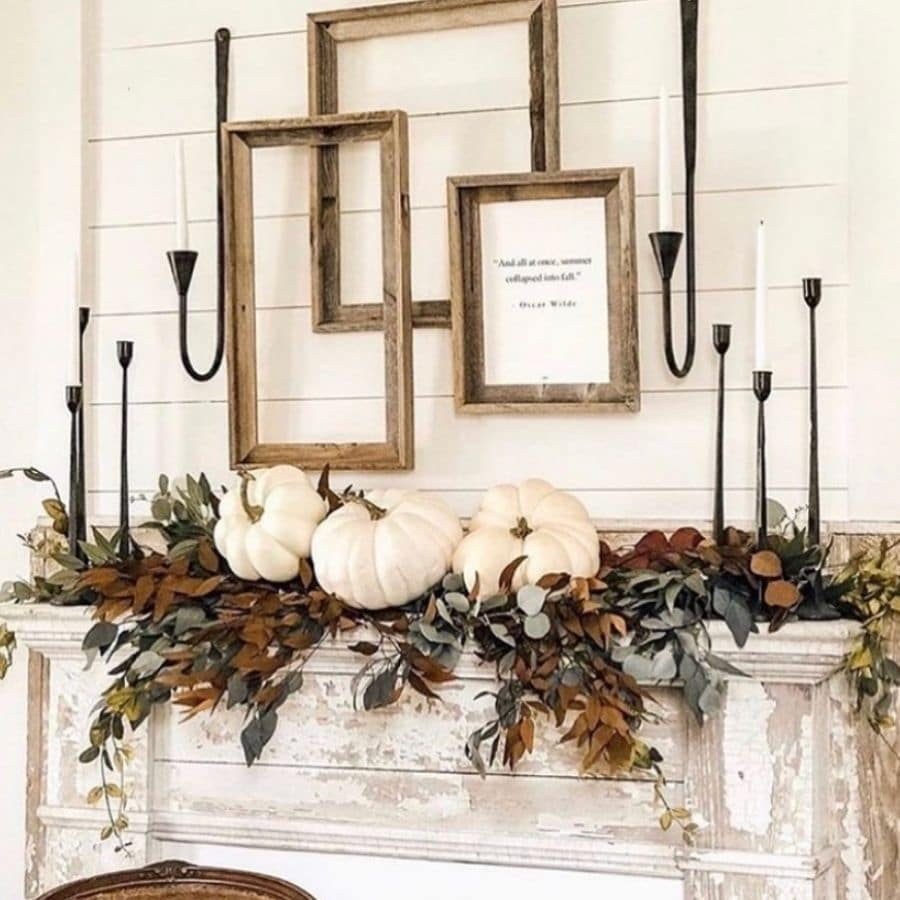 Greenery on a chippy mantle with white pumpkins sitting on top and black candle sticks on the ends.