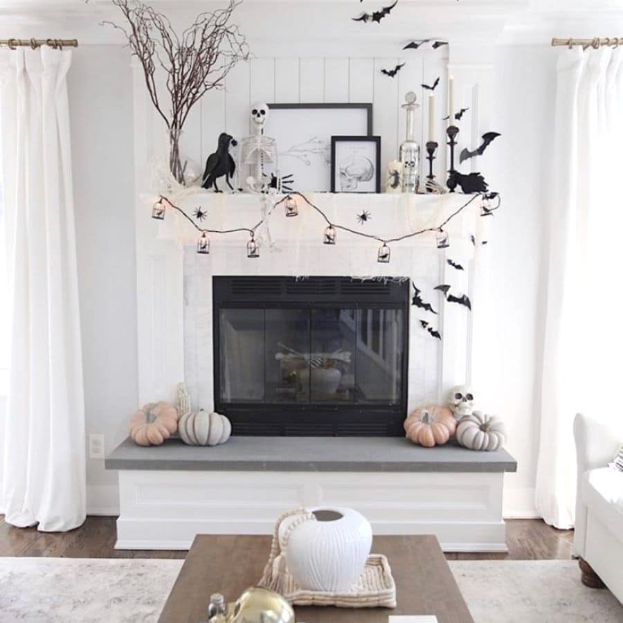 Halloween fireplace decorations in black and white and ravens, skeletons, bats, garland, candles.