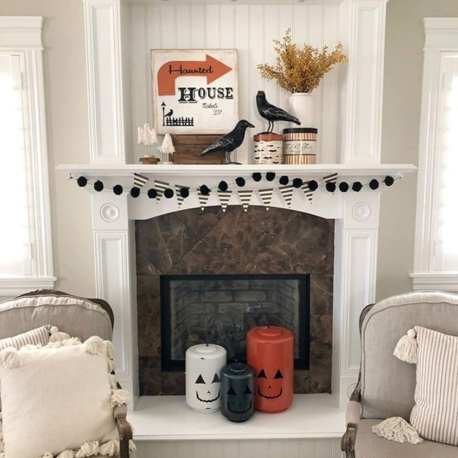 Haunted House sign, ravens, jack o lanterns, black and white garland and banner on a white fireplace mantle.
