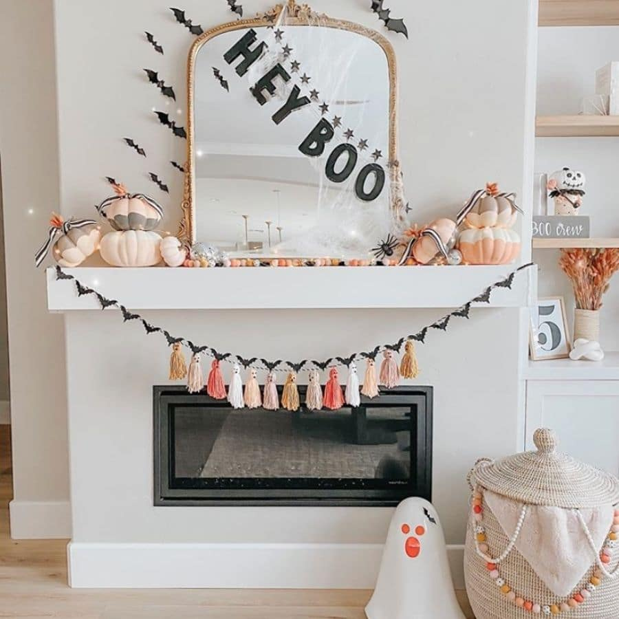 "Cute Halloween fireplace mantle ideas with bats, ""hey boo,"" ba nner, tassel garland with ghost faces, bat garland, and peach pumpkins."