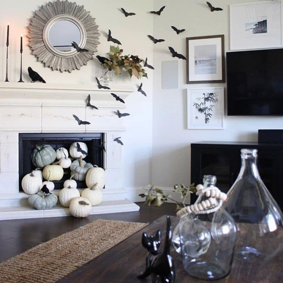 Halloween decorations for mantle with bats, pumpkins, ravens and black candles.