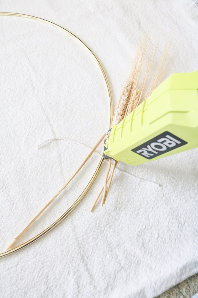 Place a dot of hot glue ton the wire ring where you will be tying the dried wheat in place.