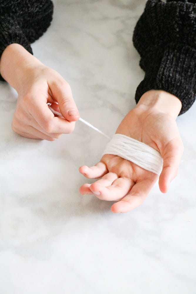 Wrap yarn around hand to make beard for Santa garland