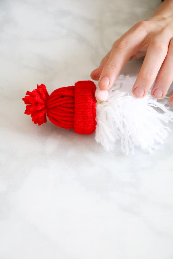 Glue a pink pom nose to the Santa beard