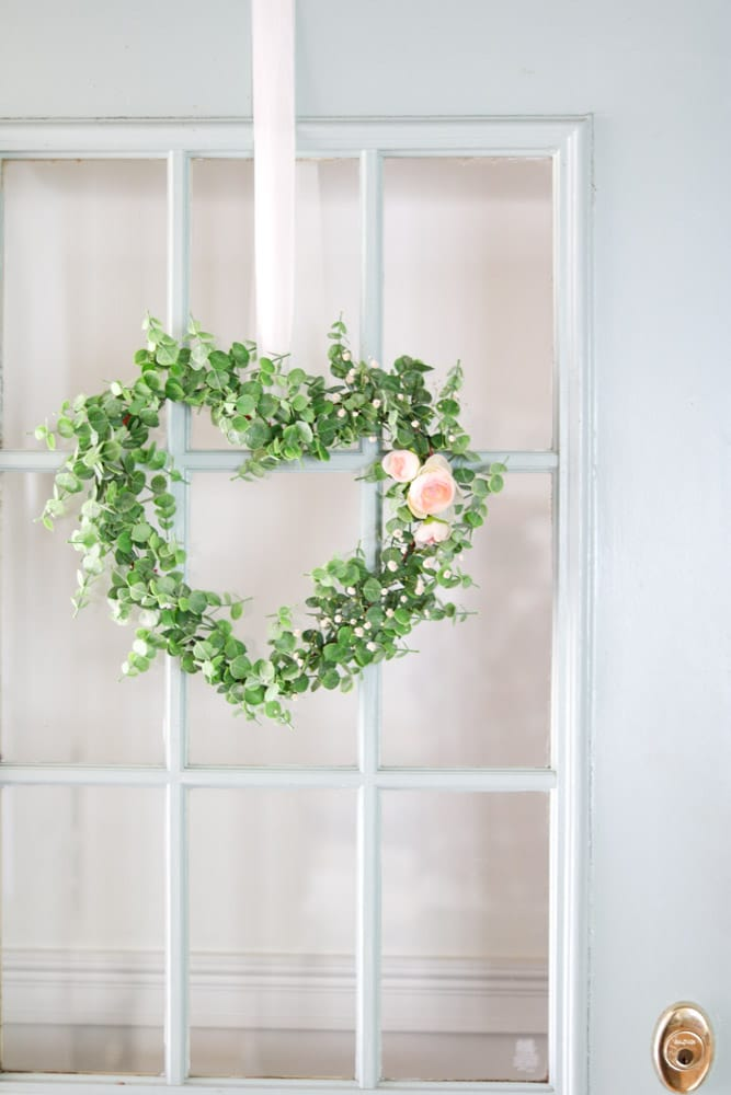 Dollar Tree DIY heart shaped floral wreath hanging on a front door