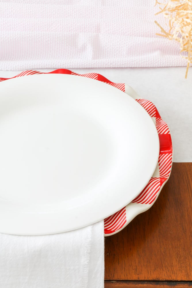 Valentine table setting with red and white buffalo check dinner plate and white plate stacked