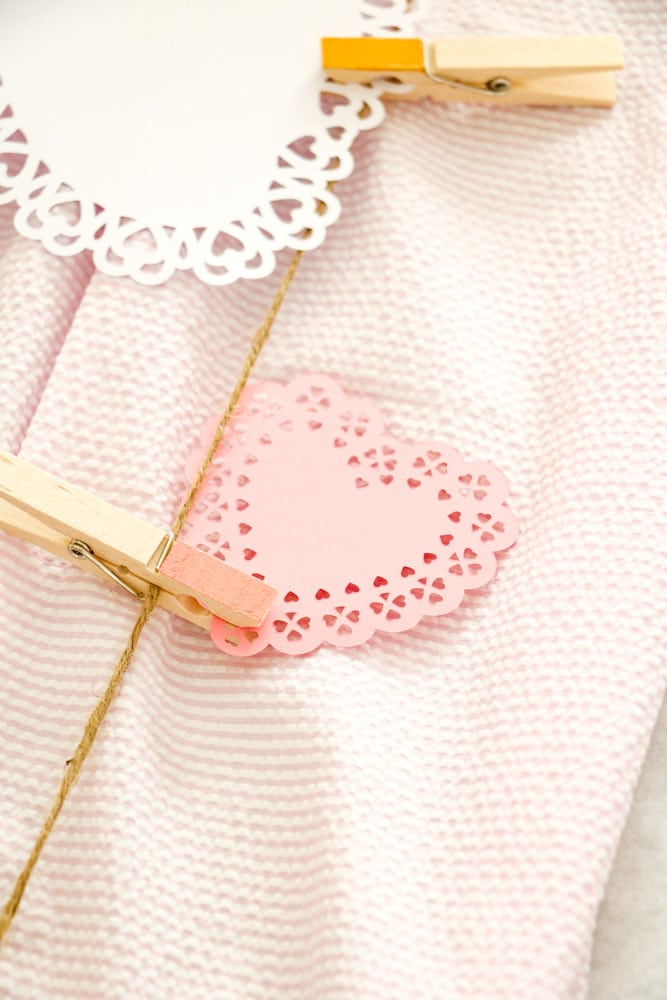 Family Valentine's day tablescape with heart doilies and clothespin table runner