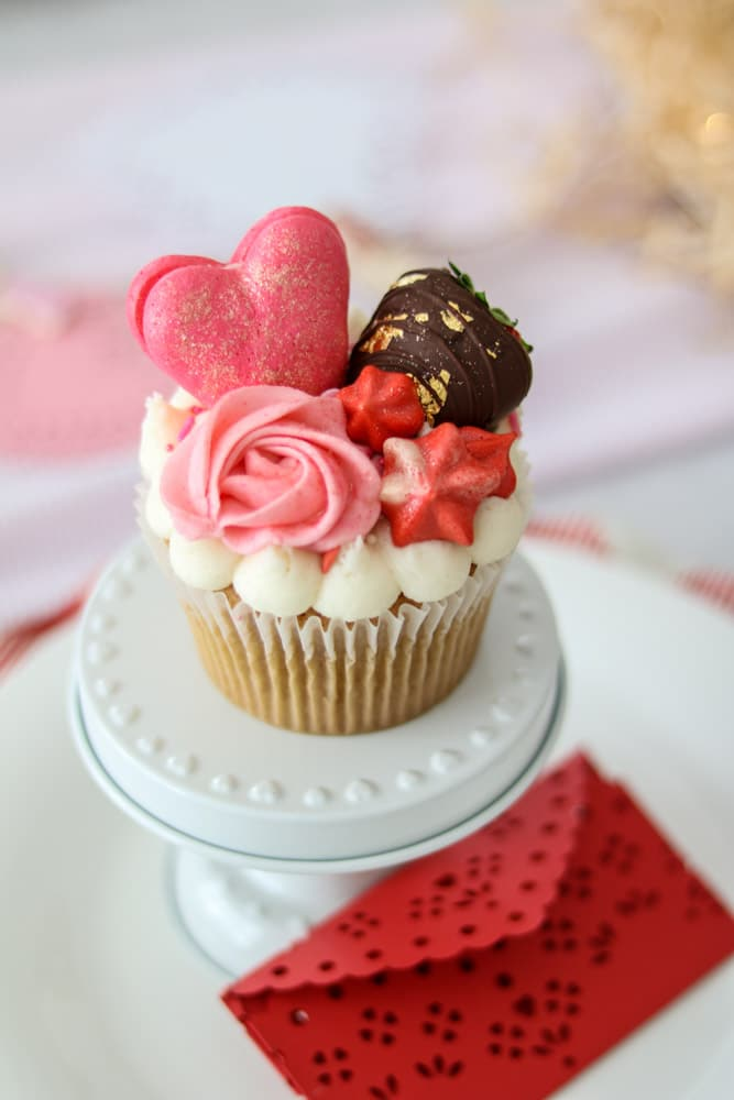 Les Cherie beautiful large cupcake with light pink icing rose, red stars, chocolate covered strawberry with gold foil and pink heart shape macaroon dusted with glitter.  Gluten and dairy free