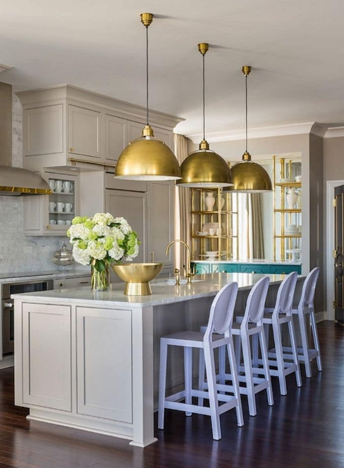 Popular Sherwin Williams cabinet colors, anew gray. A beautiful kitchen with gold dome hanging lights with matching gold accessories in this kitchen.