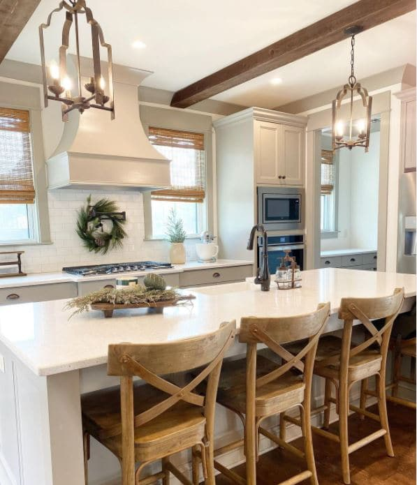 Dorian grey popular Sherwin Williams cabinet colors. A matching oven hood, fern wreath above the stove with a beautiful white granite island in the middle