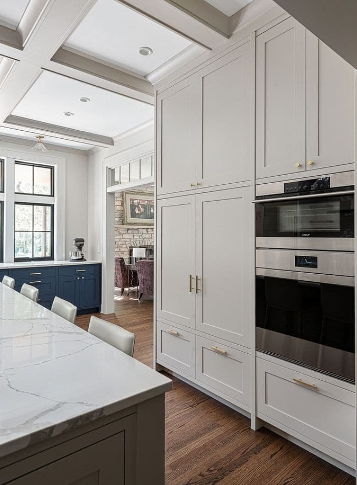 Cabinets painted with worldly gray. With beautiful gold handles and a matching gray marble kitchen island