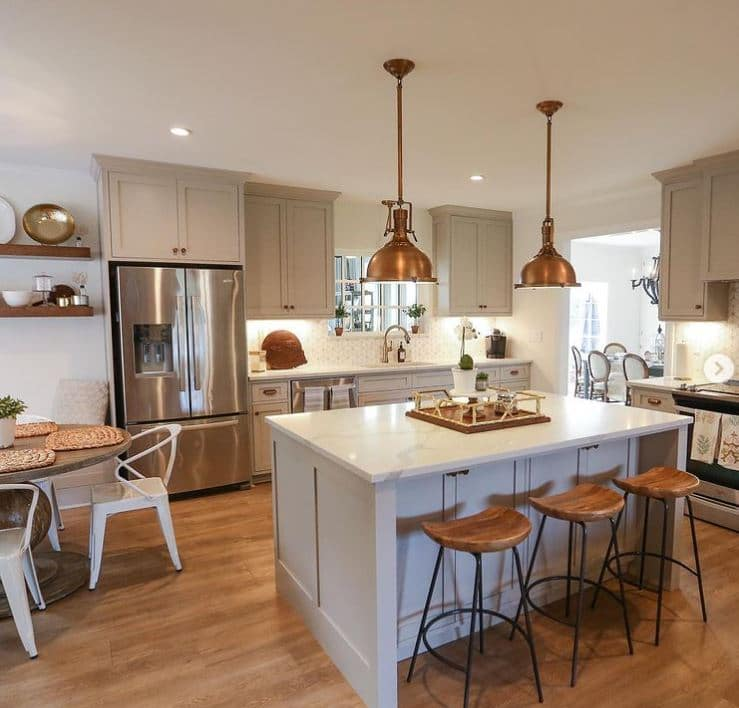 Sherwin Willaims Mindful Gray painted cabinets with rose gold hanging lights with wooden bench stools. A beautiful Marble island in the middle