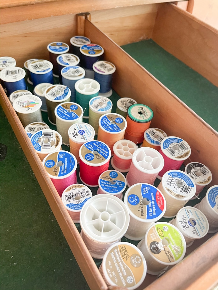 Organizing sewing supplies by rainbow color from left to right